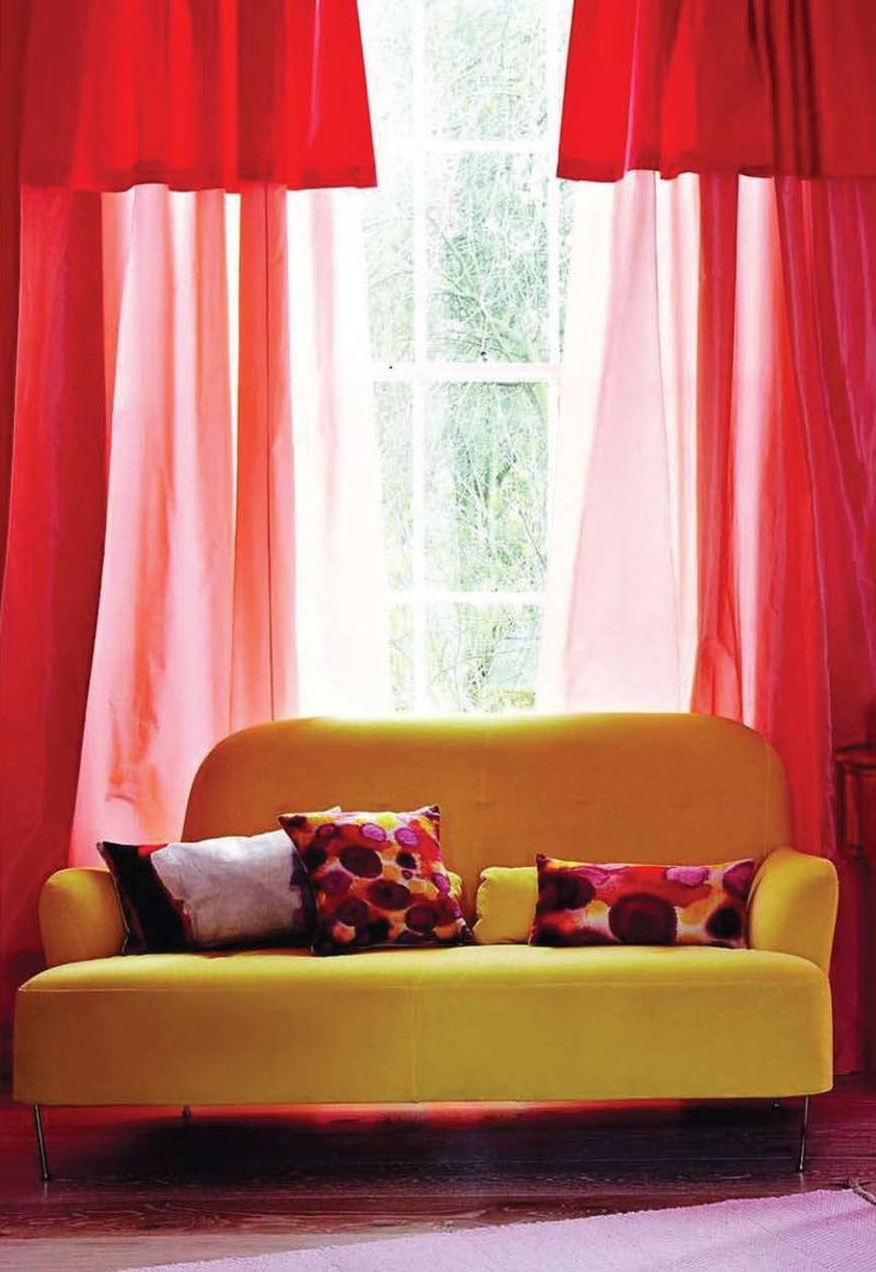 Bright yellow couch red curtains